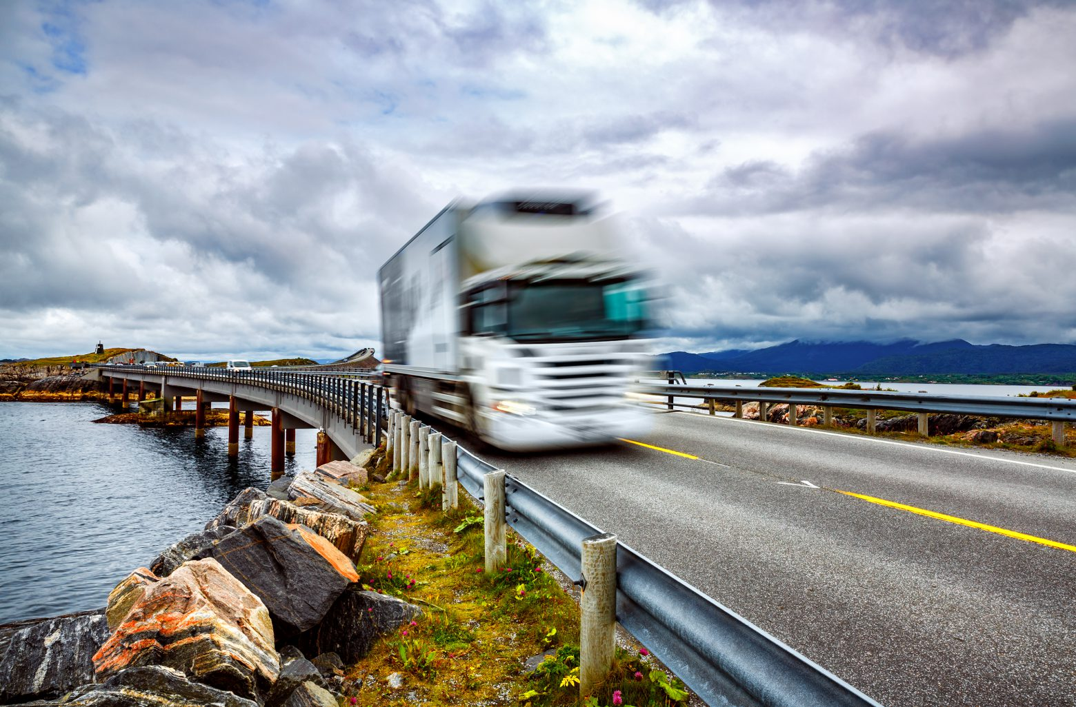 """Truck and highway at sunset. Truck Car in motion blur. Atlantic Ocean Road or the Atlantic Road (Atlanterhavsveien) been awarded the title as """"Norwegian Construction of the Century""""."""